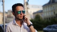 Attractive guy wearing sunglasses and talking on cellphone in the city center - stock footage