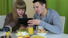 Young cheerful couple in love looking at tablet and talking over breakfast Stock Footage