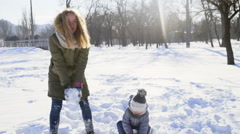 Mother and daughter trowing up some snow in the park slow motion Stock Footage