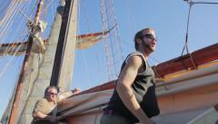 Crew member tidying up sails on a tall ship. Stock Footage