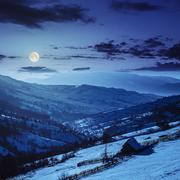 woodshed on the hillside in winter mountains at night - stock photo