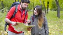 Couple of backpackers looking at the  paper map in the autumn forest Stock Footage