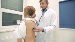 Doctor checking patient's lungs using stethoscope Stock Footage