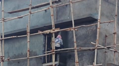 Indian construction worker works at high altitude - stock footage