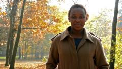 Young beautiful happy african girl stare into camera and stands in the woods  - stock footage
