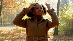 A young beautiful african girl stands in the woods and gives her loose hair.... Stock Footage