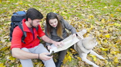 Couple of hikers and a husky dog in the autumn forest using a paper map Stock Footage