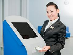 Bank worker by an ATM Stock Photos