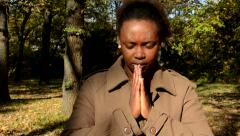 Young beautiful african girl stands in woods and whith closed eyes prays Stock Footage