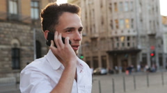 Handsome and positive guy actively talking on cellphone outdoors during sunset Stock Footage
