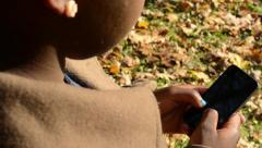 Young african girl stands in park and works on phone - detail of face Stock Footage