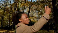 Young beautiful african happy girl stands in woods, poses and  makes selfie Stock Footage