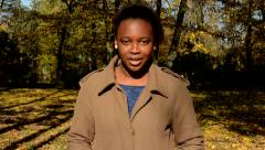 Young beautiful african calm girl stands in the woods and calmly talks  Stock Footage