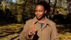 Young beautiful african serious girl stand in woods, stare to camera and shake  Stock Footage