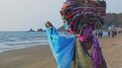 Indian woman sells traditional wears and goods on the beach in Goa Stock Footage