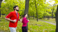 Smiling couple jogging in the autumn park slow motion Stock Footage