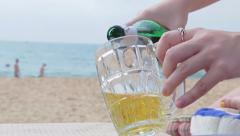 Female fills a glass of beer on the beach Stock Footage