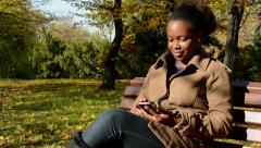 Young beautiful african happy girl sits on bench in woods, works on phone  Stock Footage