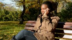 Young beautiful african happy girl sits on bench in woods and talks with someone Stock Footage