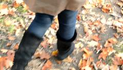 View of girl's legs in winter shoes which pass over fallen leaves Stock Footage