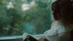 Beautiful blonde  reading a book in the train Stock Footage