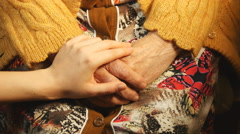 A young hand comforting a old pair of hands. Stock Footage