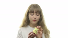 Young girl bites off apple Stock Footage