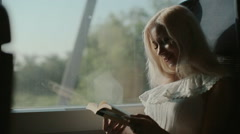 Inquisitive blonde reading a book Stock Footage