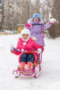 The girls in the courtyard of riding a snow sled rejoice - stock photo