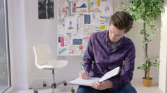 4K Worker in creative office, thinking and making notes Stock Footage
