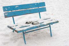 On a snow-covered bench lie forgotten childrens mittens - stock photo