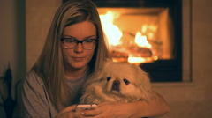 Girl with dog using phone near the fireplace - stock footage