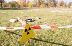 Warning radiation sign marking a hazardous radioactive area in the field. - stock photo
