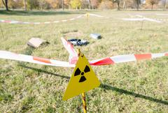 Warning radiation sign marking a hazardous radioactive area in the field. Stock Photos