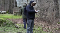 Ornithologists in the park with tablet PC and camcorder - stock footage
