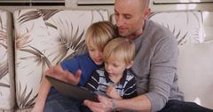 Portrait of father looking at a tablet with his two adorable sons Stock Photos