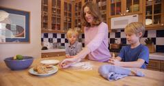Beautiful white mother preparing cookie dough with her boys - stock photo
