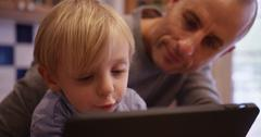 Portrait of a happy young boy reading an e-book with his father Stock Photos