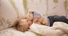 Closeup of an adorable sleepy young child lying on a sofa Stock Photos
