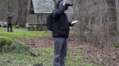Ornithologists in the park with binoculars and camcorder Stock Footage