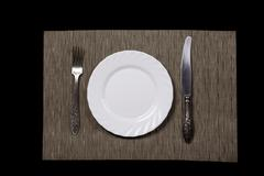 plate, spoon, knife and napkin on black background top view - stock photo
