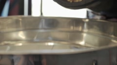 Worker add not fried coffee grains in big aluminum round cask in coffee factory Stock Footage