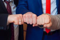 symbol of male friendship and team. Fists group of businesspeople - stock photo