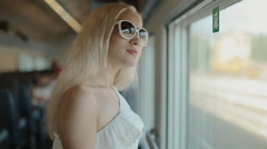 Woman in sunglasses admiring the view from the window - stock footage