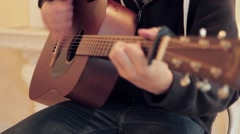 Man's hands playing acoustic guitar by mediator - stock footage