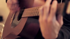 Man's hands playing acoustic guitar by mediator. Fretboard focus in out - stock footage