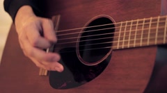 Man's hand touches on strings of acoustic guitar by mediator. Close up - stock footage