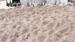 Decorated white table on sand beach in front of sea. Candles, bottles flower Stock Footage