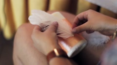 Womans hands glue white pen on big candle with orange ribbon on knees Stock Footage