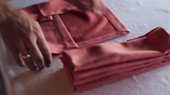 Woman hands turns red textile napkins on a table Stock Footage